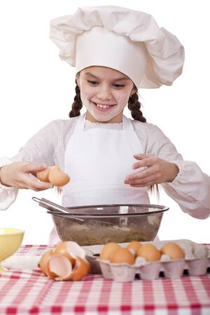 Little cook girl in a white apron breaks eggs in a deep dish, isolated on white background photo