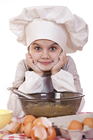 Little girl in a white apron breaks near the plate with eggs, isolated on white background photo