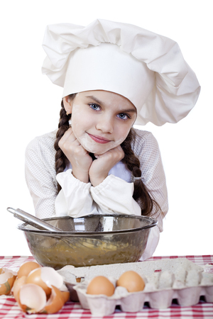 breaks: Little girl in a white apron breaks near the plate with eggs, isolated on white background