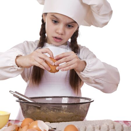breaks: Little girl in a white apron breaks eggs in a deep dish, sharpness on hand and egg Stock Photo