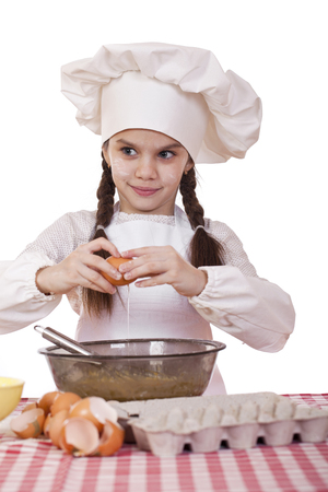 10 fingers: Little cook girl in a white apron breaks eggs in a deep dish, isolated on white background