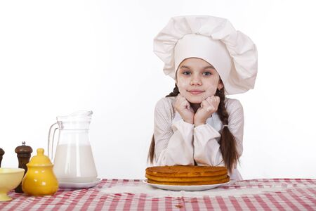 Cooking and people concept - smiling little girl in cook hat, isolated on white background photo