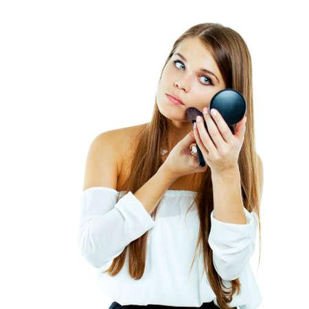 cheek to cheek: young beautiful woman applying powder on cheek with brush - isolated