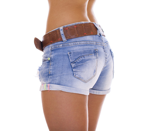 bare ass: Beautiful female legs, part of the body. Blue short denim shorts and brown boots, isolated on white background Stock Photo