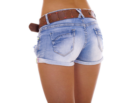 Beautiful female legs, part of the body. Blue short denim shorts and brown boots, isolated on white background photo