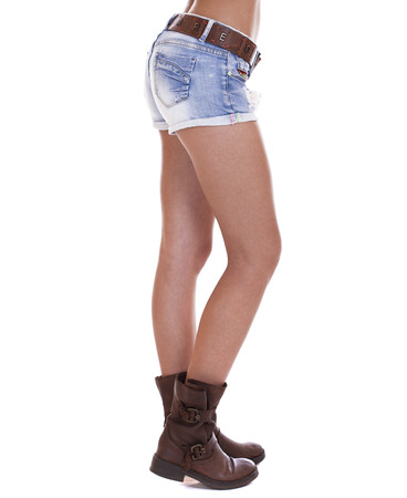 bare waist: Beautiful female legs, part of the body. Blue short denim shorts and brown boots, isolated on white background Stock Photo