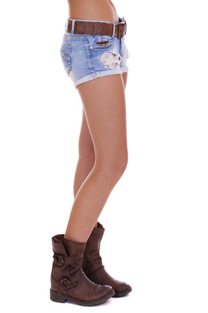 Beautiful female legs, part of the body. Blue short denim shorts and brown boots, isolated on white background Stock Photo