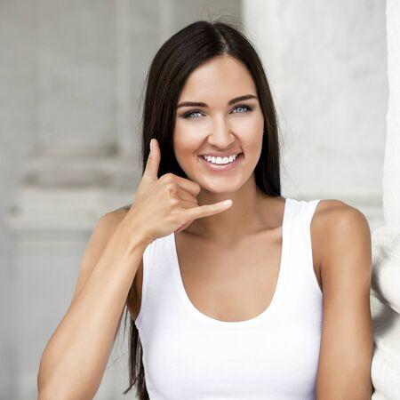 call me: Beautiful woman making a call me gesture