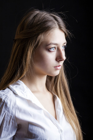 Portrait of beautiful young woman in white shirt, isolated on black background