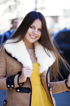 sheepskin: Portrait of a happy young girl in sheepskin coat on a background of the city Stock Photo