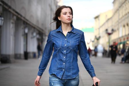 in jeans: Close up retrato de una bella mujer joven en pantalones vaqueros camisa azul en el fondo de la calle del resorte
