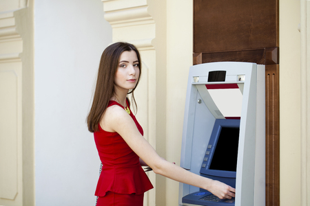 checking account: Brunette young lady using an automated teller machine . Woman withdrawing money or checking account balance Stock Photo