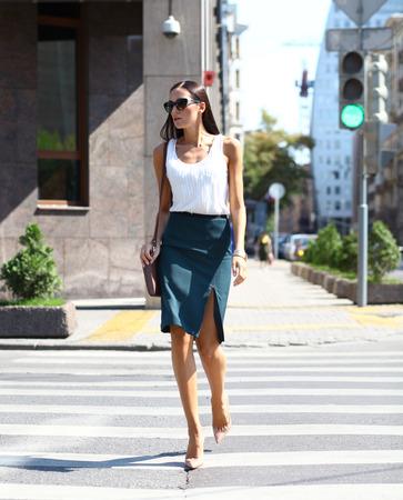 dia soleado: Mujer de negocios que cruza la carretera fuera en un d�a soleado Foto de archivo