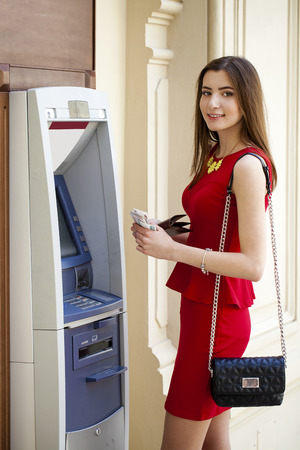 woman red dress: Brunette young lady using an automated teller machine . Woman withdrawing money or checking account balance Stock Photo