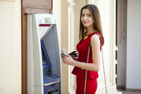Brunette young lady using an automated teller machine . Woman withdrawing money or checking account balance Banque d'images