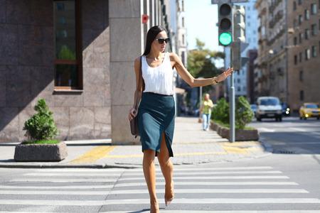 semaforo peatonal: Mujer de negocios que cruza la carretera fuera en un día soleado Foto de archivo