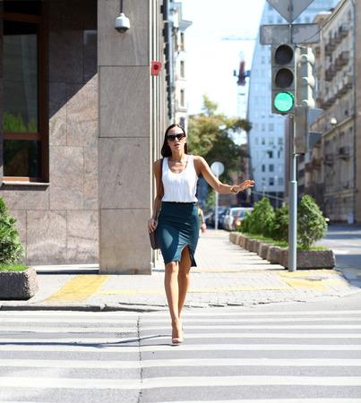 semaforo peatonal: Mujer de negocios que cruza la carretera fuera en un d�a soleado Foto de archivo