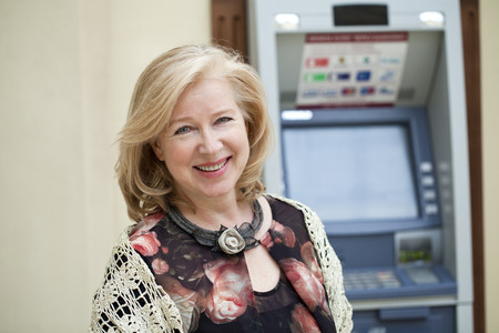 automated teller: Happy Mature blonde woman near automated teller machine in shop