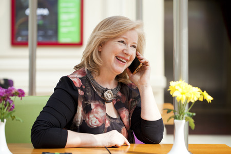 Mature beautiful blonde woman is calling on a cell phone while sitting in a coffee shop Foto de archivo