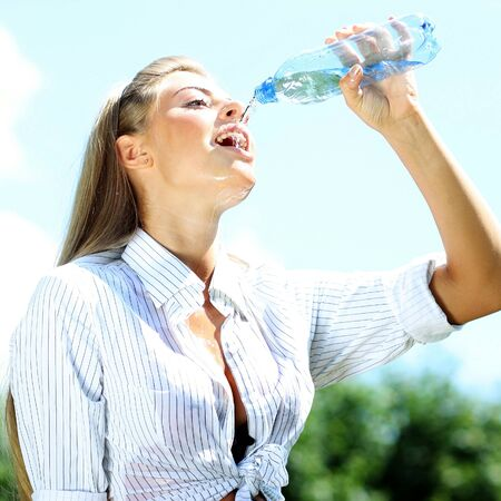 Sexy young woman drinking water from a bottle photo