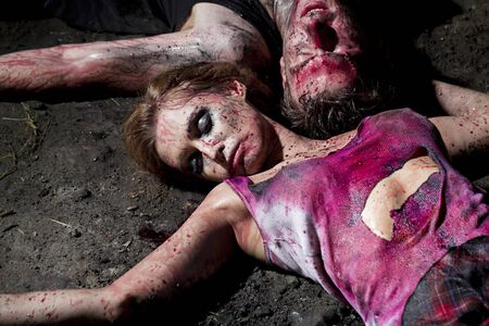 Couple of bloody man and woman lying on the ground photo