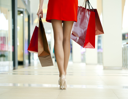personal shopper: Legs of shopaholic wearing red dress while carrying several paperbags