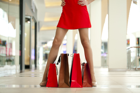 paperbags: Legs of shopaholic wearing red dress while carrying several paperbags