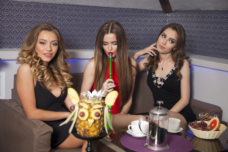 russian girl: Beauty portrait of young three sexy women resting in the hookah room