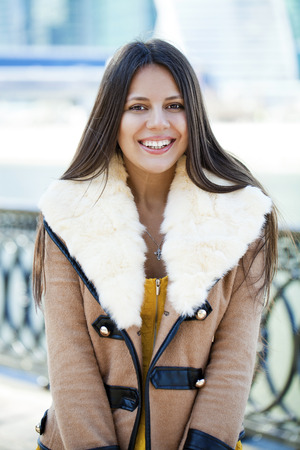 Portrait of a happy young girl in sheepskin coat on a background of the city Stock Photo