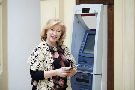 cash slips: Mature blonde woman counting money near automated teller machine in shop