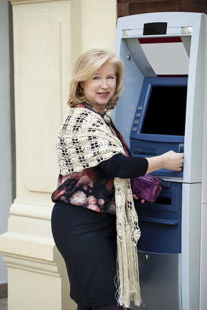 cash slips: Mature blonde woman with credit card in hand near automated teller machine in shop Stock Photo