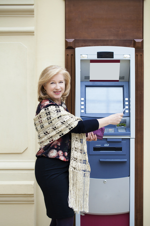 automated teller machine: Mature blonde woman with credit card in hand near automated teller machine in shop Stock Photo