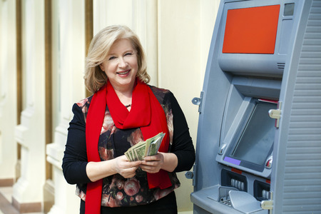 cash dispenser: Mature blonde woman counting money near automated teller machine in shop