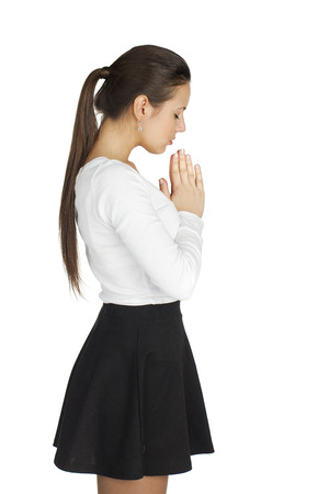 orison: Young woman standing for white background with her hands folded and eyes closed, praying. Stock Photo