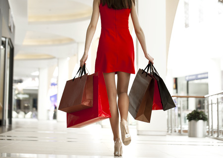 가게에서 산책 쇼핑 가방을 들고 빨간 드레스에 아름 다운 젊은 여자,