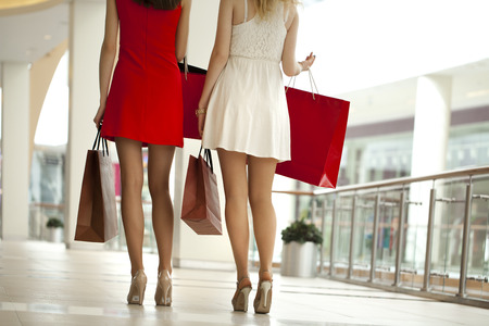 personal shopper: Two pairs of female legs with shopping bags in their hands Stock Photo
