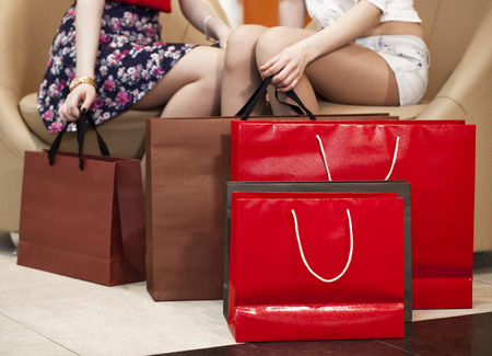 personal shopper: Two pairs of female legs with shopping bags