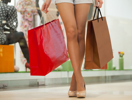 paperbags: Close up Legs of shopaholic wearing jeans shorts while carrying several paperbags