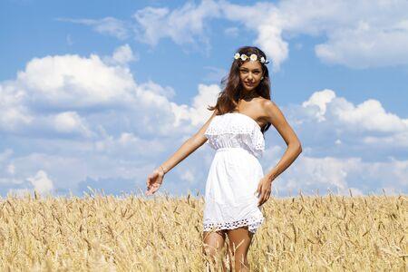 vestido blanco: Joven y bella mujer en vestido blanco en el campo de trigo de oro