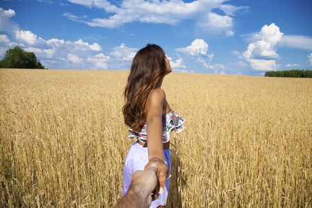 Follow me, Beautiful sexy young woman holds the hand of a man in a wheat field photo