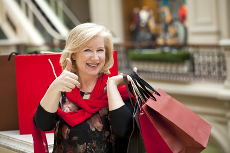 woman arms up: Mature happy blonde woman with shopping bags
