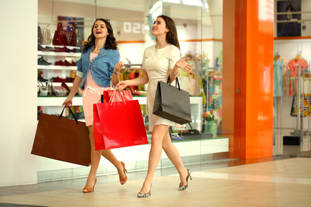 Two young girls walking with shopping at the store