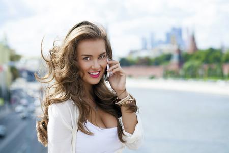 Gelukkig mooi meisje belt via de telefoon in een zomer op straat