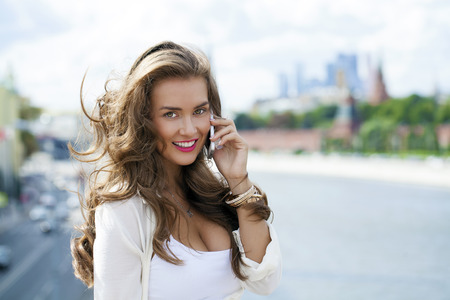 Happy beautiful girl calling by phone in a summer street Standard-Bild