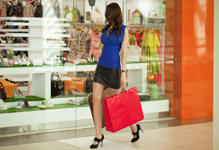 Beautiful young woman in black skirt, holding shopping bags walking in the shop photo