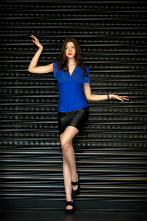 louver: Young sexy woman in black skirt and blue blouse on the background of steel louver Stock Photo