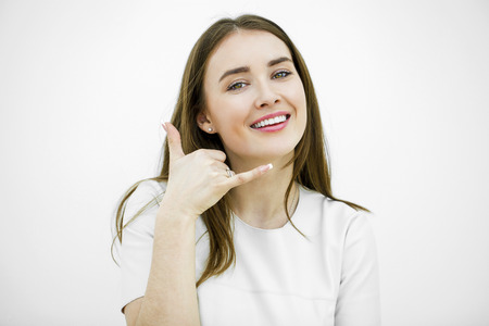 call me: Young happy smiling brunette woman with call me gesture, against white background Stock Photo
