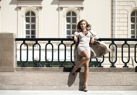 Portrait in full growth, Young beautiful blonde woman in beige coat posing outdoors in sunny weather