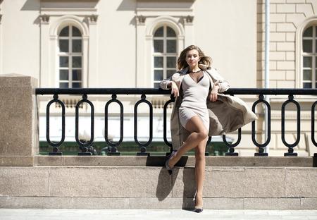 donna sexy: Ritratto in piena crescita, Giovane bella donna bionda in cappotto beige posa all'aperto in tempo soleggiato