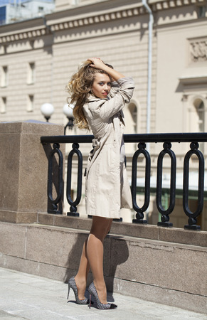 full height: Portrait in full growth, Young beautiful blonde woman in beige coat posing outdoors in sunny weather